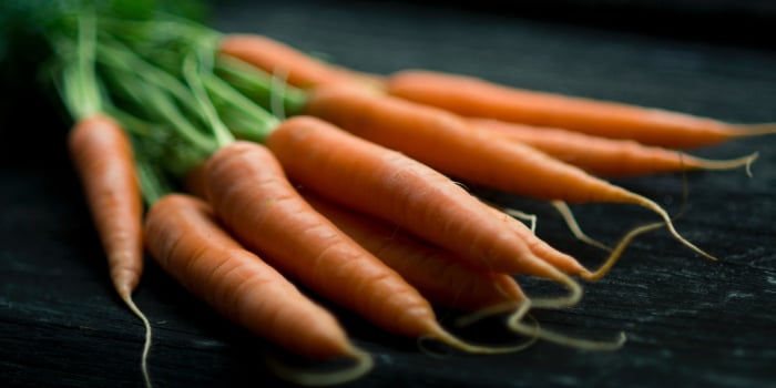 Cluster of tooth-healthy orange carrots with green stems against a dark counter